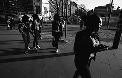 Street scenes (__ _) Tags: girls people blackandwhite film composition contrast finland dark evening helsinki europe streetphotography tones ilford underexposed greys decisivemoment obscure vappu 1stofmay panf selfdeveloped panfplus harshsunlight homedevelopment percptol movingby
