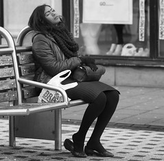 Kick off the shoes, lay back the head, and... (Just Ard) Tags: street people blackandwhite bw woman white black blancoynegro girl monochrome face bench person photography mono nikon noiretblanc zwartwit candid 85mm d750 resting unposed  biancoenero dozing schwarzundweis