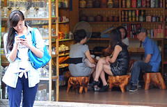 Interaction (Andy WXx2009) Tags: china street girls people urban sexy men beauty fashion shopping store women asia sitting highheels shanghai legs candid femme streetphotography style meeting doorway mobilephone bags brunette stool minidress crosslegged asiangirls