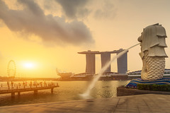 Sunrise in the morning at Singapore Marina Bay (Krunja) Tags: park city morning travel light sunset sky sun water statue skyline sunrise river landscape singapore asia view outdoor background famous lion landmark business merlion attraction marinabay clouddy