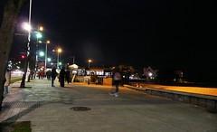 Coruña by night - Strolling along the seafront promenade towards ´Playa Club´. (Dirk Bontenbal) Tags: city nightphotography sea people urban blur beach water night reflections walking noche mar seaside coruña streetphotography ciudad playa noflash panasonic galicia citylights handheld urbano atlanticocean notripod atlántico reflejos unsharp lacoruña riazor borroso urbantexture lucesdeciudad dmctz3 riazorbeach flashapagado galiciaatlantica