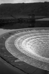 Ladybower Reservoir (l4ts) Tags: landscape blackwhite derwentvalley derbyshire peakdistrict olympusxa2 winhill darkpeak filmscan overflowing spillway ladybowerreservoir valvehouse vuescan nikoncoolscaniv britnatparks blackwhitenegativefilm kentmere100film