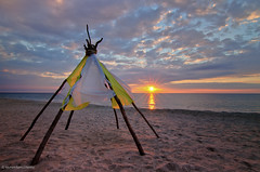 Welcoming the sun (yevhen-s) Tags: ocean wood old sunset sea sky sun house west heritage history home pee silhouette skyline illustration night clouds sunrise dawn sand native dusk background indian traditional culture nobody columbia tent basin lodge american western land prairie teepee tradition aboriginal tribe shelter tee seacoast indigenous nightfall wigwam dwelling