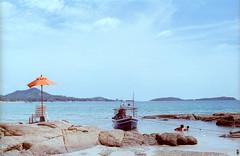 Boat on a beach (sunnylapin) Tags: ocean blue sea summer film beach water umbrella thailand boat sand siam canonfd canonfx