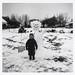 Little boy stands next to a snowman and shovel