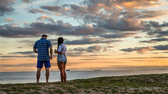 Man and woman enjoying the sunset, St Kilda Beach, Melbourne (trevorjphotography) Tags: friends sunset sky seascape water clouds landscape happy seaside couple candid ships horizon cellphone lifestyle peaceful australia melbourne victoria romance lovers frombehind mobilephone oceanview manandwoman stkildabeach shortshorts portphillipbay maleandfemale beachgoers boyfriendandgirlfriend ef24105mmf4lisusm backtocamera canoneos5dmarkii shortsandtshirt checkingphone