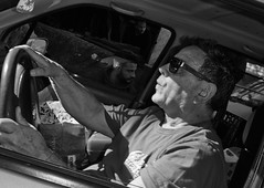 Drive by. (Baz 120) Tags: life street city portrait people urban blackandwhite bw italy rome roma monochrome mono europe italia faces candid strangers streetphotography streetportrait olympus monotone streetphoto manual unposed streetfaces omd decisivemoment candidportrait candidphotography m43 streetcandid mft streetphotograph primelens em5 romestreets romepeople candidstreet zonefocusing candidface flashstreetphotography olympus17mm romecandid grittystreetphotography