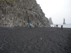 A shot that Mary took of me on Reynisfjara, with the Reynisdrangar stacks and Stulaberg basalt columns ahead of me (Anosmia) Tags: mountain blacksand iceland vik sland basalt seastack vk strnd stulaberg fjara blacksandbeach reynisfjara reynisdrangar sandar reynisfjall volcanicsand landdrangur hidrangur skessudrangur langhamar