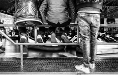 Two up, one down. (Mister G.C.) Tags: street people urban blackandwhite bw men feet monochrome standing deutschland shoes europe sitting legs fairground candid young streetphotography guys fair sneakers trainers jeans frombehind males 20mm unposed bumpercars schwarzweiss dodgems funpark youths denims niedersachsen lowersaxony autoscooter pancakelens primelens sonyalpha mirrorless zonefocusing strassenfotografie manualfocusing sel20f28 sonya6000