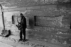 Man with a horn (sadrollieman) Tags: street nyc travel bw music usa man brick film america overpass tunnel horn sax f5