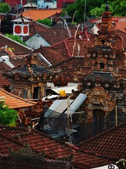 the yellow parasol (SM Tham) Tags: trees bali umbrella indonesia outdoors island temple town construction rooftops bricks towers parasol gateway netting kuta rooftiles corrugatedsheets