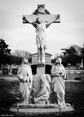 St. Mary's Cemetery (Gabrielle Gaia) Tags: blackandwhite sculpture cemetery grave graveyard statue illinois catholic cross jesus il crucifix stmary peoria jesuschrist calvary stmaryscemetery catholiccemetery westpeoria
