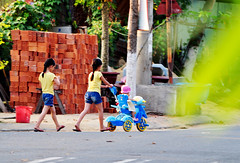 Twins and baby (Roving I) Tags: street girls walking children twins babies bricks vietnam greenery matching plaits danang strollers identical