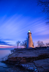 Beneath a Starry Sky (souravzzz) Tags: longexposure ohio sky lighthouse lake tree beach water night clouds stars dawn lights rocks wideangle