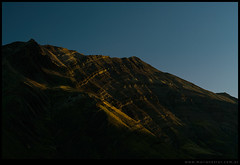 Luces acarician un cerro al amanecer