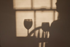 Sun through the Cafe Window (brucetopher) Tags: light shadow people sunlight window glass silhouette relax person chair wine peaceful calm wineglass relaxation relaxed throughthewindow