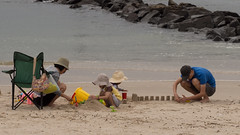 On the Beach 3 (Mariasme) Tags: family people beach water children parents sand hats sandcastles groyne