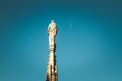 Divine (Nuuttipukki) Tags: blue sky italy milan statue airplane object milano divine duomo