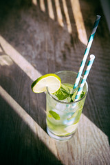 cold mojito cocktail with ice and straw on board (coolnina) Tags: summer sunlight cold color green ice water glass leaf vibrant object board mint naturallight fresh cocktail drinks twig mojito citrus lime mohito refreshing beverages straws refreshment