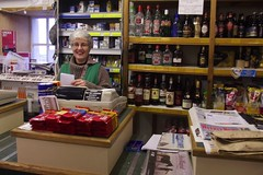 Jane, Ulsta Store, Yell, Shetland (junk shop cafe) Tags: woman smiling shop ferry lady port shopping island happy glasses scotland newspaper wine diesel harbour newspapers alcohol whisky vernacular petrol cigarettes groceries yell cornershop shetland fuel conveniencestore petrolstation shopkeeper groceryshop shetlander ulsta