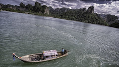 longtail departure (Eddy Alvarez) Tags: travel sky mountain thailand island boat asia cliffs exotic southeast phuket longtail andamansea poda phiphiislands