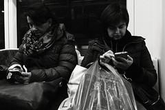 Women with Phones (Kojotisko) Tags: bw streetphotography brno creativecommons czechrepublic streetphoto panasoniclumixdmcft2 lumixdmcft2