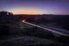 A drive through the valley (daniel_munch) Tags: longexposure sunset tree grass car forest denmark dusk hill hills valley lighttrails magical rebild abigfave
