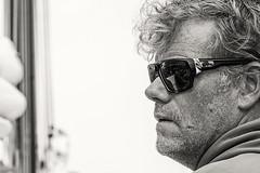 Der Skipper (Panasonikon) Tags: portrait bw skipper seemann segeln segeltörn nikond7100 brille sonnenbrille dreitagebart hansesail abeltasman panasonikon nikkor6028 explore schärfentiefe sw