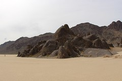 Actual size of human and The Grandstand (daveynin) Tags: rock desert nps playa deathvalley monolith partlycloudy drylakebed