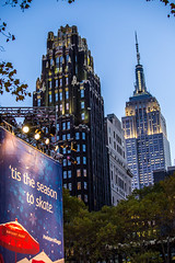 Bryant Hotel, The Empire State Building and a Billboard for the Ice Skating in Bryant Park, New York City, USA ([ PsycBob ]) Tags: park winter light sunset building ice hotel licht sonnenuntergang village state skating billboard empire bryant the bryanthotel