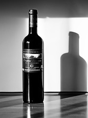 Greek Bottle Of The Red Wine From Corfu (be.image photography) Tags: shadow red blackandwhite bw sunlight kitchen monochrome vertical closeup greek wooden european wine drink interior label dry nopeople full made greece alcohol corfu kerkyra tabletop winemaking refreshment