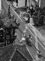 a family outing (SM Tham) Tags: road street family roof decorations blackandwhite bali woman plants man monochrome buildings indonesia outdoors temple child motorbike cables gateway shops kuta rooftiles