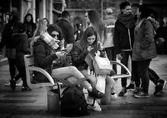 Oblivious (Just Ard) Tags: street people blackandwhite bw woman white black blancoynegro girl monochrome face mobile bench person photography mono nikon sitting phone noiretblanc zwartwit candid 85mm d750 bags unposed  biancoenero schwarzundweis justard