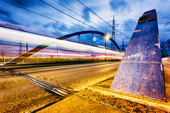 speed demon (Blende57) Tags: road street longexposure bridge light urban motion metal night speed canal streetlight nightlights nightscape pavement steel tram blurred motionblur transportation urbanphotography blurredmotion inlandwaterway steelconstruction lightstars