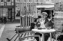 A seat at last. (Mister G.C.) Tags: old city people urban blackandwhite bw woman coffee monochrome lady deutschland town cafe europe sitting image candid seat streetphotography photograph elderly 20mm unposed schwarzweiss streetshot niedersachsen lowersaxony outdoorcafe pancakelens primelens sonyalpha mirrorless zonefocusing zonefocus strassenfotografie sel20f28 sonya6000 mistergc