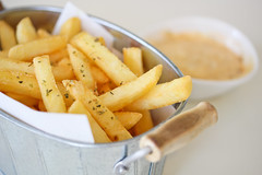 Tasty french fries on table background (diary of moon) Tags: food green glass yellow closeup french table lunch golden wooden fry cone background napkin fat board rustic salt fast wrapped tasty fresh container delicious crispy eat potato crisps pile snack rosemary meal fatty cutting jar chip diet crunchy unhealthy calories prepared salted fattening