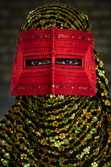 a bandari woman wearing a traditional mask called the burqa, Hormozgan, Minab, Iran (Eric Lafforgue) Tags: red portrait people woman beauty vertical golden persian clothing eyes asia veil mask iran muslim islam religion hijab culture persia headshot hidden indoors covered iranian adultsonly oneperson traditionaldress burqa customs middleeastern frontview sunni burka chador 20sadult youngadultwoman balouch hormozgan onewomanonly lookingatcamera burqua  bandari  embroidering 1people  iro thursdaymarket  minab colourpicture  borqe panjshambebazar boregheh irandsc06755