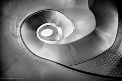 Round and Round to The Gallery (Edwinjones) Tags: city uk greatbritain light england urban bw building london art lines architecture modern stairs photoshop mono blackwhite shiny europe gallery shine unitedkingdom steel interior bricks curves wideangle line lookingup well indoors staircase gb banister elegant curve hdr spiralstaircase topaz hirst photomatix helical damianhirst dslra700 newportstreetgallery