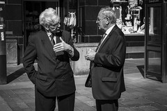 The Business Of Business (Leanne Boulton) Tags: life street city uk light shadow portrait people urban blackandwhite bw white man black detail male men texture monochrome face work canon mono scotland living blackwhite shadows hand faces natural humanity outdoor expression glasgow candid culture streetphotography tie streetlife scene business suit human shade 7d expressive conversation gesture society trade tone facial interaction candidportrait candidstreetphotography