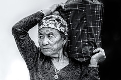 Old age in black and white (Axel Halbgebauer) Tags: old travel nepal portrait people blackandwhite bw woman white black face zeiss bag blackwhite hands asia dof head background candid sony age fe wrinkles pokhara carry sonnar sonnar13518za
