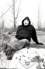 """""""V"""" on a Old Caddy (PhotoJester40) Tags: blackandwhite male outside outdoors mask modeling guyfawkes relaxing posing v junkyard bnw naturalsetting"""
