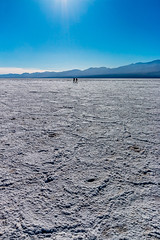Death Valley NP | Badwater Basin Salt Flats (Facundity) Tags: california blue white mountains nature vertical crust landscape outdoors nationalpark haze outdoor salt silhouettes naturallight saltflats sunflare badwater badwaterbasin deathvalleynp belowsealevel verticallandscape 190cxpro3 canoneos70d