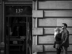 137 (Leanne Boulton) Tags: life street city uk light shadow people urban blackandwhite bw woman white man black detail male texture love monochrome face look wall loving female composition canon 50mm mono scotland living blackwhite couple faces natural emotion humanity outdoor expression glasgow candid culture streetphotography streetlife scene romance doorway human together shade 7d blonde feeling closeness embrace society tone facial candidstreetphotography