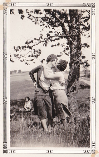 Two women kissing next to a tree