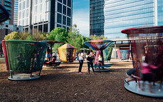 whirled (almostsummersky) Tags: travel trees windows people sunlight art glass buildings children us spring rainbow downtown texas afternoon unitedstates spin crowd houston exhibit installation spinning interactive tops threads woodchips whirl discoverygreen lostrompos