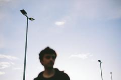some more blur (.Till) Tags: blue portrait sky blur guy face clouds streetlight bokeh parking lot pole bielefeld