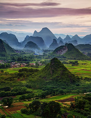 A Misty Evening In China (Stuck in Customs) Tags: china pink brown blur mountains color colour green june vertical fog clouds river haze soft village view purple guilin sony horizon rr hills gradient limestone karst dailyphoto trey tangdynasty 2014 ratcliff southeastchina p2016 treyratcliff lakecedar stuckincustomscom ilce7r lakebanyan xiqinglake