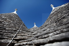 Stone waves (Elios.k) Tags: camera travel blue roof summer vacation sky italy house distortion color colour building travelling tourism weather horizontal stone architecture canon outdoors photography town carved focus dof angle cone traditional wide perspective august cable nopeople unesco worldheritagesite depthoffield clear hut shape trulli salento puglia bari pinnacle conical trullo whitewashed alberobello apulia 2015 pinnacolo foregroundblur 5dmkii
