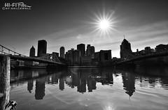 Beacon of Light (Hi-Fi Fotos) Tags: city urban blackandwhite bw sun reflection water skyline river mono nikon pittsburgh north wide bridges ducks calm tokina shore edge flare allegheny d5000 1120mm hallewell hififotos tokinaaf1120mmf28