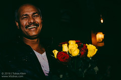 The Rose Peddler (kle.tobias) Tags: street red roses portrait rose yellow night laughing out fun 50mm lights nikon candid athens portraiture laugh shooting hustler peddler d610